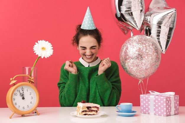 Vrolijke jonge nerd student meisje viert haar verjaardag en verheugt zich zittend bij de tafel