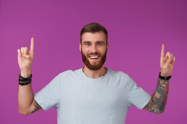 Vrolijke jonge ongeschoren getatoeëerde man met kort kapsel, gekleed in een blauw t-shirt terwijl hij op paars staat, met een brede, gelukkige glimlach en zijn wijsvingers opheft