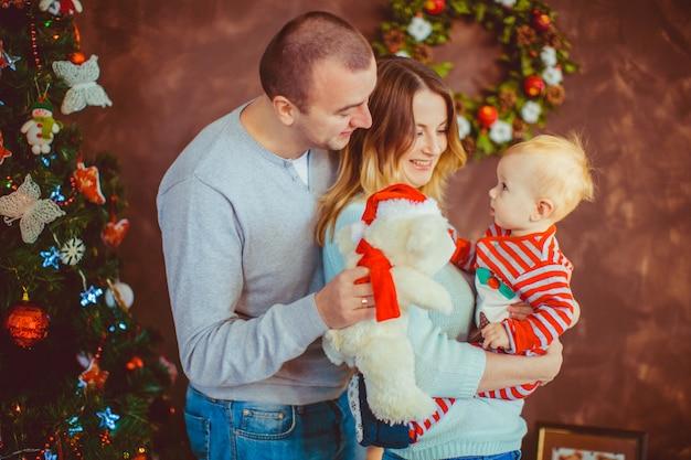 Vrolijke jonge ouders houden een klein kind poseren voor een kerstboom