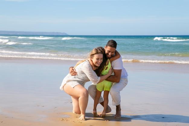 Vrolijke jonge ouders knuffelen dochtertje