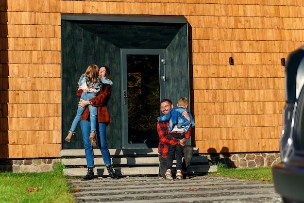 Vrolijke jonge ouders ontmoeten en knuffelen hun lieve kinderen op de veranda van het huis. gelukkig gezin