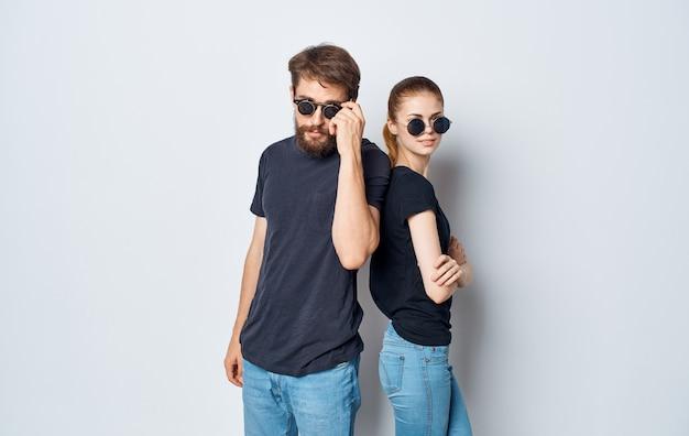 Vrolijke jonge paar dragen zonnebril vrijetijdskleding studio mededeling