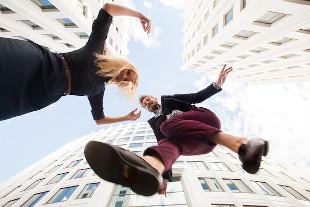 Vrolijke jonge paar gek rond, springen op de achtergrond van het gebouw. onderaanzicht
