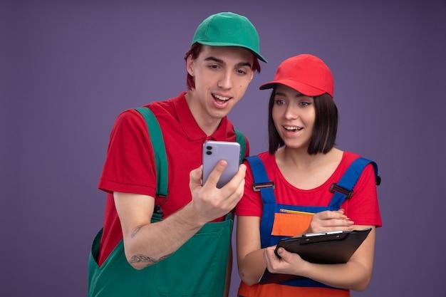 Vrolijke jonge paar in bouwvakker uniform en cap man met mobiele telefoon meisje met potlood en klembord beide kijken naar mobiele telefoon geïsoleerd op paarse muur