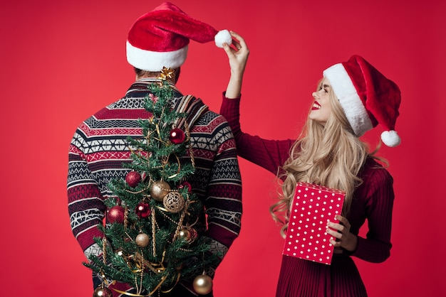 Vrolijke jonge paar in santa hoeden kerstboom speelgoed decoraties. hoge kwaliteit foto