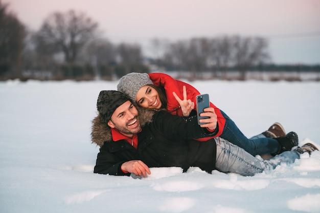 Vrolijke jonge paar in warme kleren liggen samen in de sneeuw en nemen selfie op smartphone terwijl ze plezier hebben in de winterlandschap