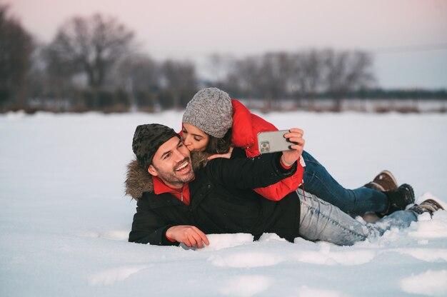 Vrolijke jonge paar in warme kleren liggen samen in de sneeuw en nemen selfie op smartphone terwijl ze plezier hebben in de winterlandschap Premium Foto