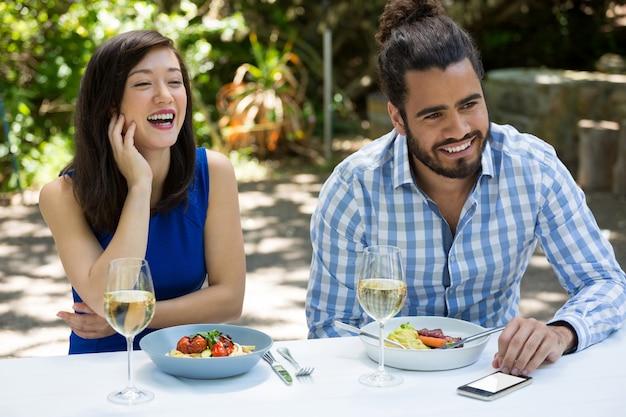 Vrolijke jonge paar lunchen in openluchtrestaurant