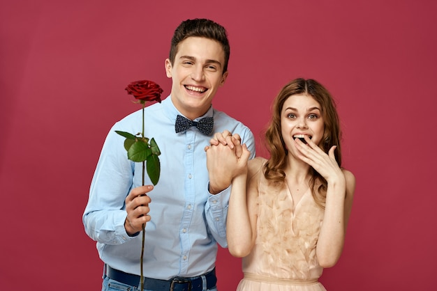 Vrolijke jonge paar omhelzing rode roos geïsoleerd te houden