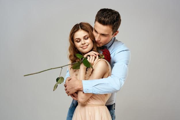 Vrolijke jonge paar romantiek omhelzen relatie rode roos levensstijl lichte achtergrond. hoge kwaliteit foto