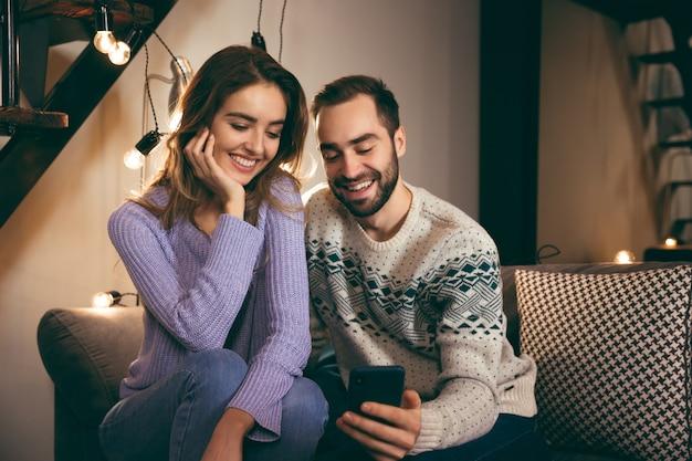 Vrolijke jonge paar samen zitten op een bank thuis, een selfie te nemen