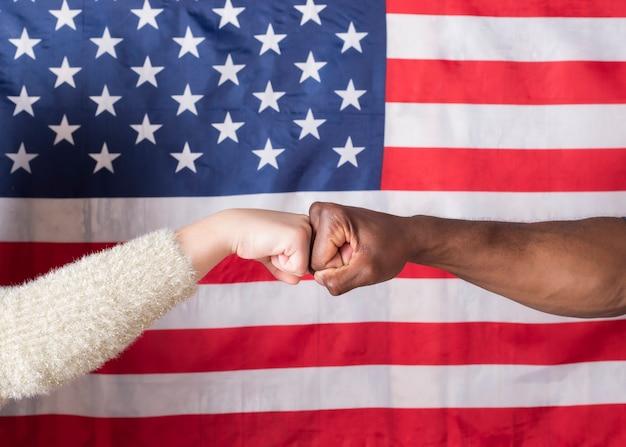Vrolijke jonge paar twee vrienden jongen meisje over usa vlag. mensen levensstijl concept. vuistbultjes geven