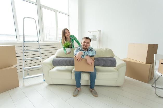 Vrolijke jonge paar verheugt zich in de verhuizing naar een nieuw huis met hun bezittingen in de woonkamer. concept van housewarming en hypotheken voor een jong gezin.