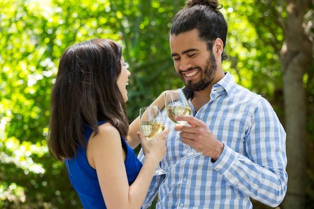 Vrolijke jonge paar wijnglazen roosteren in park