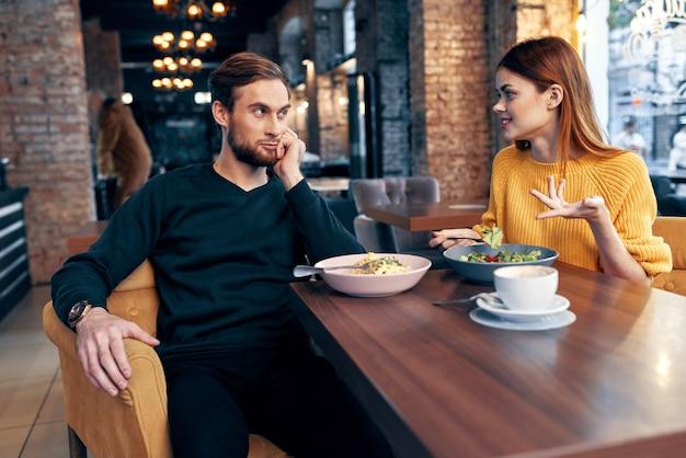Vrolijke jonge paar zitten in een restaurant rest eten