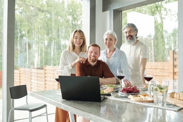 Vrolijke jonge paar zittend op de bank en zwaaiende handen naar laptop tijdens het chatten via videoverbinding in de woonkamer van cottage house