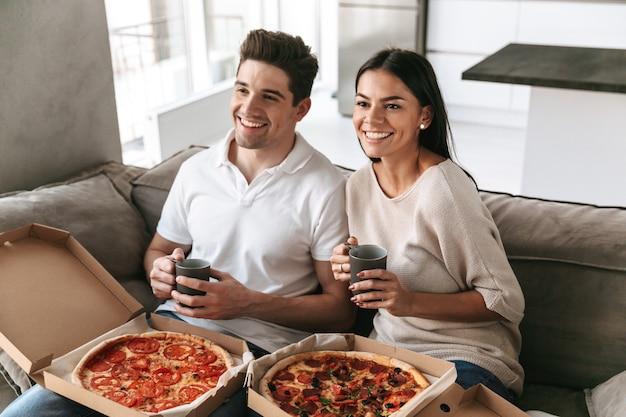 Vrolijke jonge paar zittend op een bank thuis, pizza eten