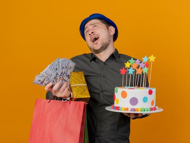 Vrolijke jonge partij kerel die blauwe hoed draagt die cake met giften en geld houdt die op oranje wordt geïsoleerd