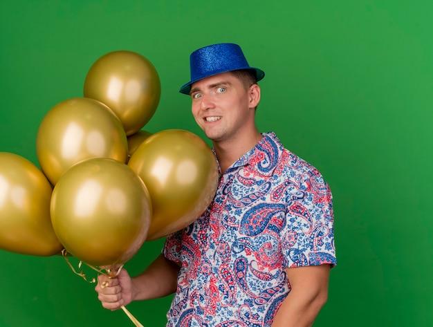 Vrolijke jonge partijkerel die de blauwe ballons van de hoedenholding draagt die op groen worden geïsoleerd