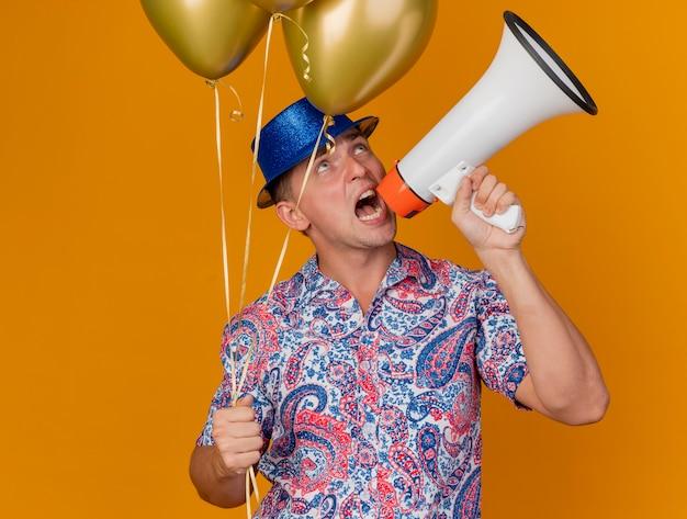 Vrolijke jonge partijkerel die de blauwe ballons van de hoedholding draagt en op luidspreker spreekt die op oranje wordt geïsoleerd
