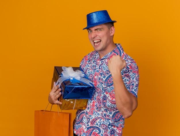 Vrolijke jonge partijkerel die de blauwe giftdozen van de hoedholding met zak draagt die ja gebaar toont dat op oranje wordt geïsoleerd