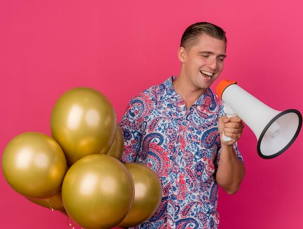 Vrolijke jonge partijkerel die kant bekijkt die kleurrijke ballons van de overhemdsholding kijkt en op luidspreker spreekt die op roze wordt geïsoleerd
