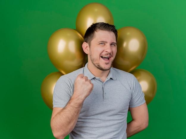 Vrolijke jonge partijkerel die verjaardag glb draagt die zich voor ballons bevindt en ja festure toont dat op groen wordt geïsoleerd