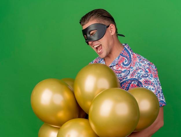 Vrolijke jonge partijkerel met gesloten ogen die de holdingsballons van het maskeradeoogmasker dragen die op groen worden geïsoleerd