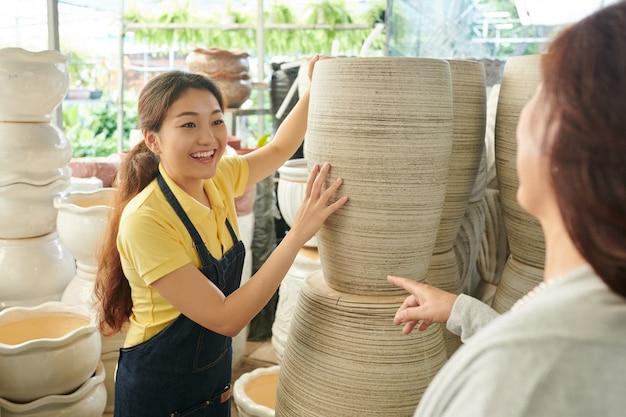 Vrolijke jonge plantenwinkelmanager die de klant de grootste bloempot laat zien die ze in petto hebben