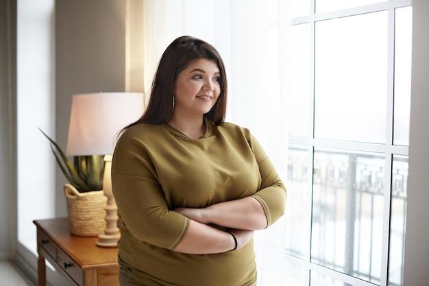 Vrolijke jonge plus size overgewicht vrouw met zwart haar en mollige wangen die de armen op haar borst kruisen en gelukkig glimlachen, bij het raam staan, naar buiten kijken, overweegt mooi ochtendzicht