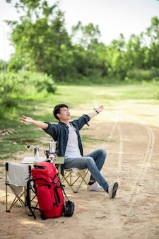 Vrolijke jonge reiziger man zit aan de voorkant van de tent in het bos met koffieset en het maken van verse koffiemolen tijdens het kamperen op zomervakantie