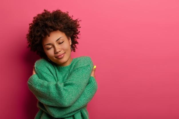 Vrolijke jonge romantische vrouw drukt zelfliefde en zorgzaamheid uit, kantelt het hoofd en glimlacht zachtjes