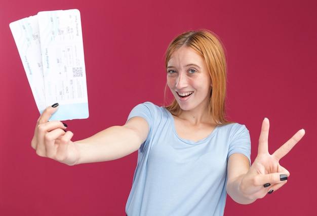 Vrolijke jonge roodharige gember meisje met sproeten gebaren overwinning teken en houden van vliegtickets geïsoleerd op roze muur met kopie ruimte
