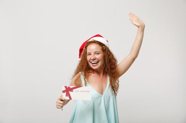 Vrolijke jonge roodharige santa meisje in lichte kleding, kerstmuts geïsoleerd op een witte achtergrond. gelukkig nieuwjaar 2020 viering vakantie concept. bespotten kopie ruimte. houd cadeaubon vast, stijgende hand.