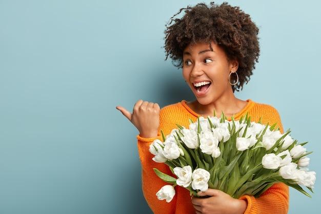 Vrolijke jonge schattige vrouw met donkere huid en krullend haar, wijst met de duim naar links, wijst de richting van de bloemist, houdt mooie witte lentebloemen vast, draagt een oranje trui, geïsoleerd over een blauwe muur.