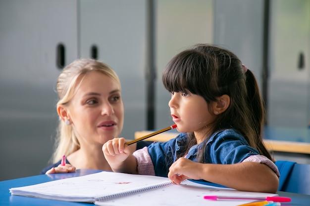 Vrolijke jonge schoolleraar die weinig schoolmeisje helpt om haar taak te doen