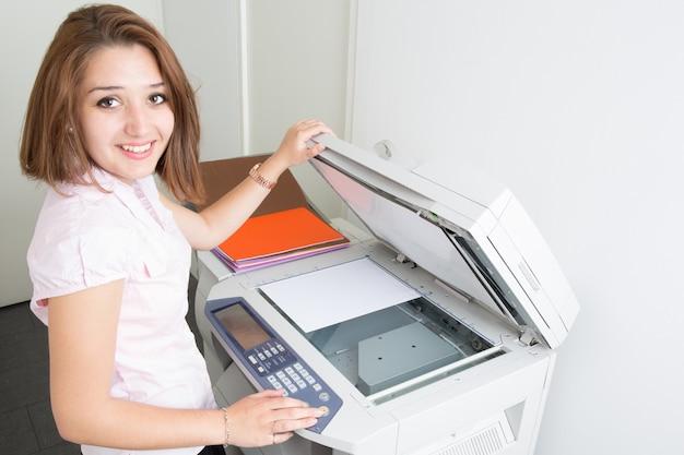 Vrolijke jonge secretaresse met behulp van een kopieermachine