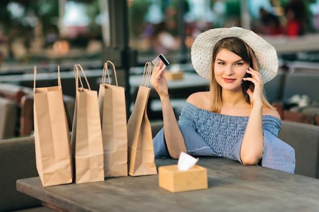 Vrolijke jonge shopaholic vrouwenzitting in openluchtkoffie terwijl het spreken op de telefoon en het houden van bankpas in haar hand