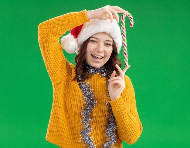 Vrolijke jonge slavische meisje met kerstmuts en met guirlande om de nek met snoepgoed geïsoleerd op groene muur met kopieerruimte