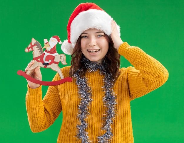 Vrolijke jonge slavische meisje met kerstmuts en met slinger om de nek houdt de kerstman op hobbelpaarddecoratie en legt de hand op het hoofd geïsoleerd op de groene muur met kopieerruimte