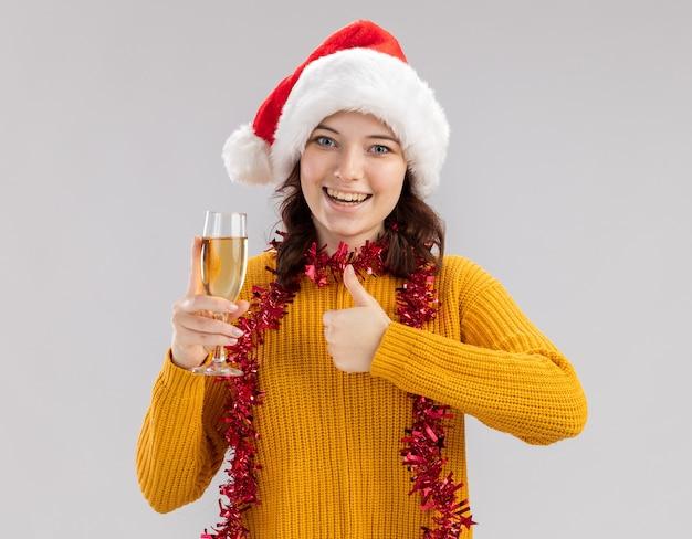 Vrolijke jonge slavische meisje met kerstmuts en met slinger om de nek met glas champagne en duimen omhoog geïsoleerd op een witte muur met kopie ruimte