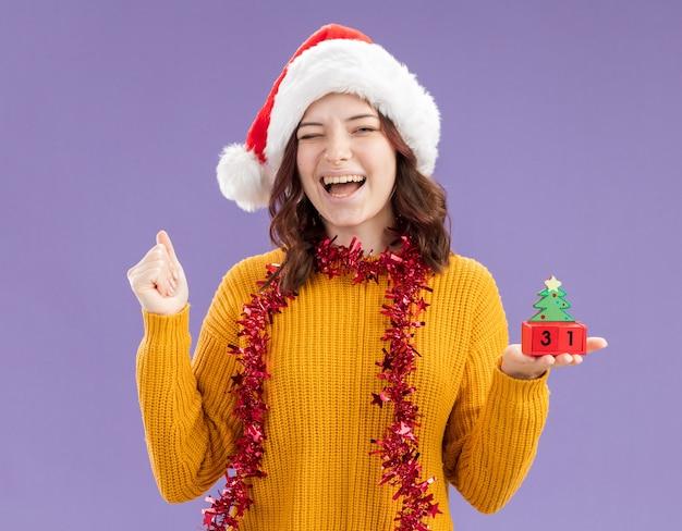Vrolijke jonge slavische meisje met kerstmuts en met slinger om nek knippert oog en houdt kerstboom ornament geïsoleerd op paarse achtergrond met kopie ruimte