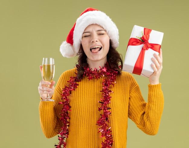 Vrolijke jonge slavische meisje met kerstmuts en met slinger rond de nek steekt tong uit met glas champagne en kerst geschenkdoos geïsoleerd op olijfgroene achtergrond met kopie ruimte