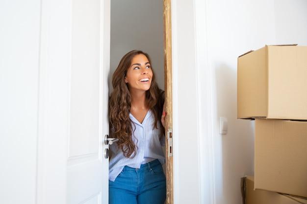Vrolijke jonge spaanse vrouw verhuizen naar een nieuw appartement, deur openen, permanent in deuropening, stapel kartonnen dozen kijken en glimlachen