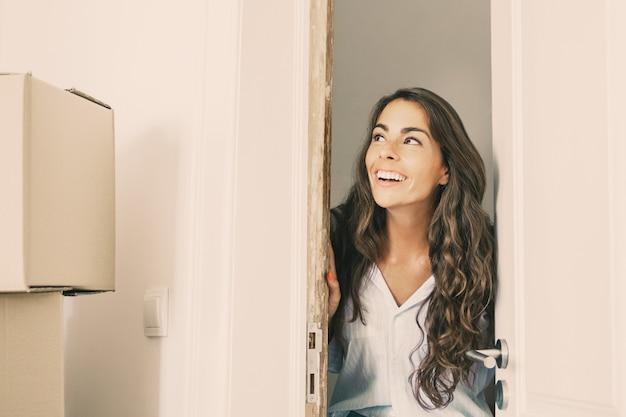 Vrolijke jonge spaanse vrouw verhuizen naar nieuw appartement, deur openen, permanent in deuropening
