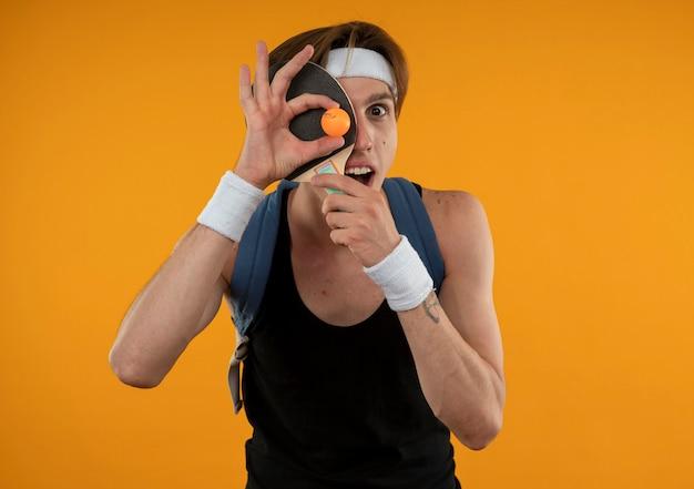 Vrolijke jonge sportieve kerel die rugzak met hoofdband en polsbandje draagt bedekt gezicht met pingpongracket en bal geïsoleerd op oranje muur