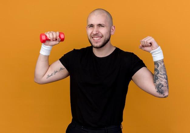Vrolijke jonge sportieve man die de halter van de polsband houdt en sterk gebaar doet dat op oranje achtergrond wordt geïsoleerd