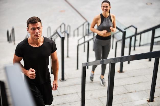 Vrolijke jonge sportieve man en vrouw brengen actieve tijd door in de stad en rennen naar boven
