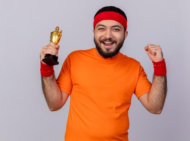 Vrolijke jonge sportieve man met hoofdband en polsbandje houden winnaar beker weergegeven: sterk gebaar geïsoleerd op een witte achtergrond