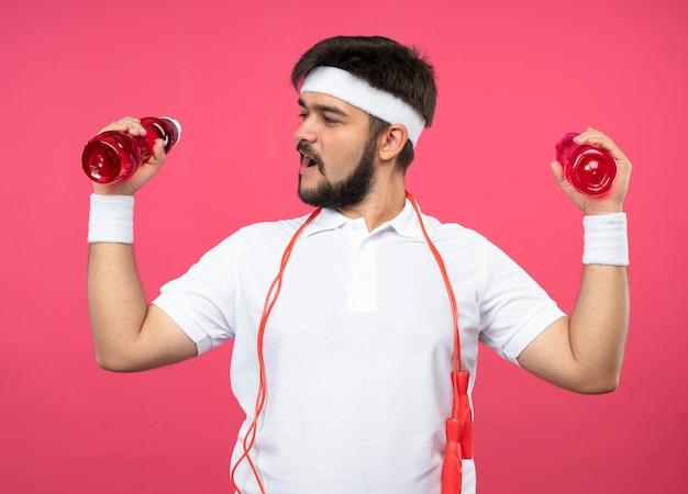 Vrolijke jonge sportieve man met hoofdband en polsbandje met waterfles met springtouw op schouder